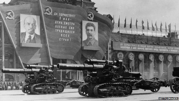 Heavy artillery on parade passing posters of Lenin and Stalin, 1947