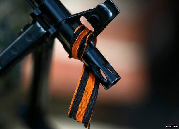 Black and orange ribbon tied around the barrel of a gun