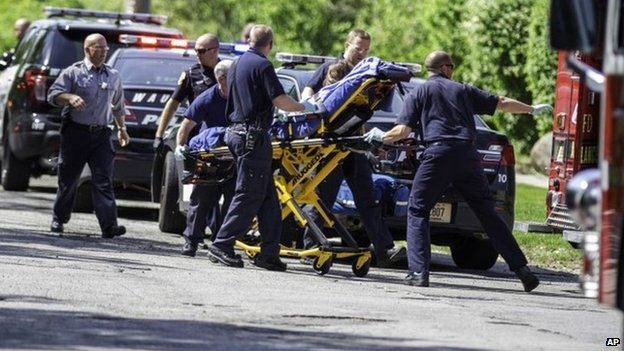 Rescue workers take a stabbing victim to the ambulance in Waukesha, Wisconsin 31 May 2014