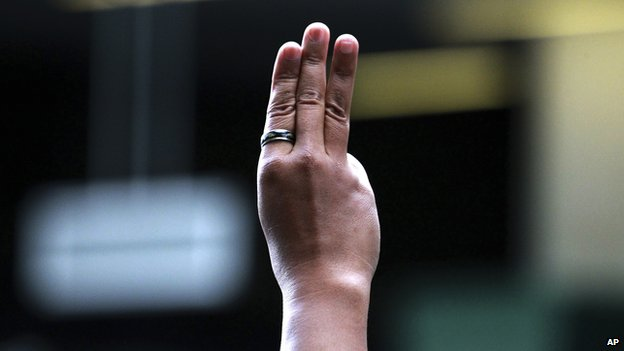 A protester flashes three fingers, representing liberty, brotherhood and equality, during an anti-coup demonstration at a shopping mall in Bangkok (1 June 2014)