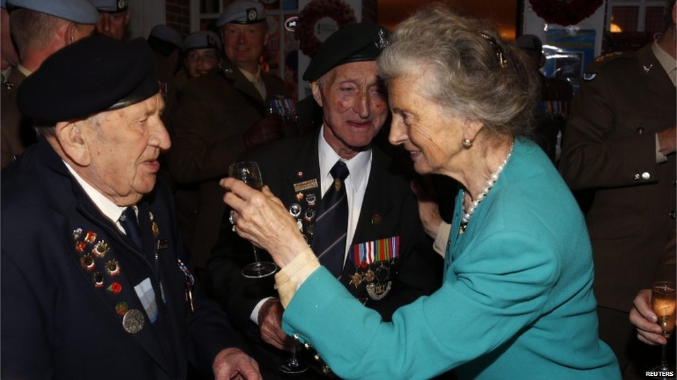 A woman raises a glass to two UK veterans