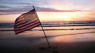A US flag planted on a beach