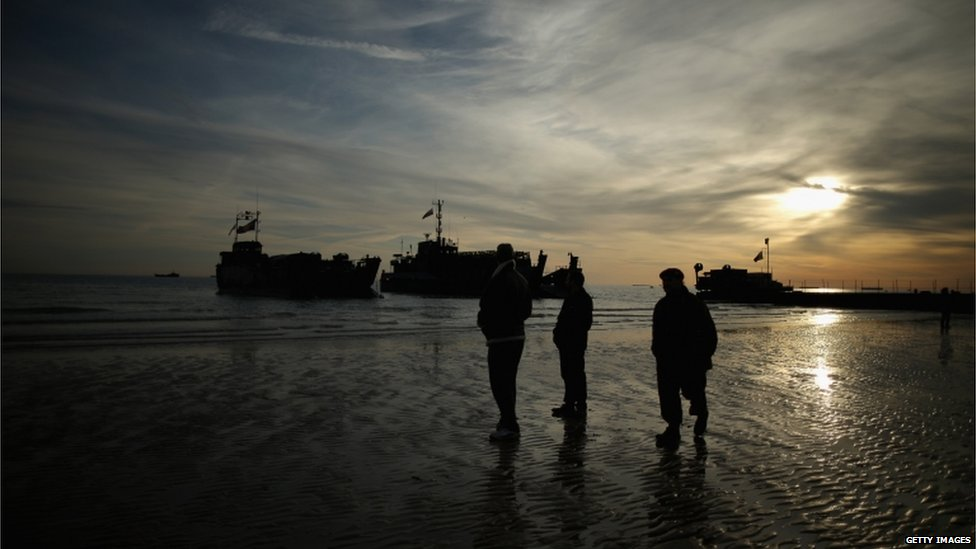 Landing craft and soldiers on a beach