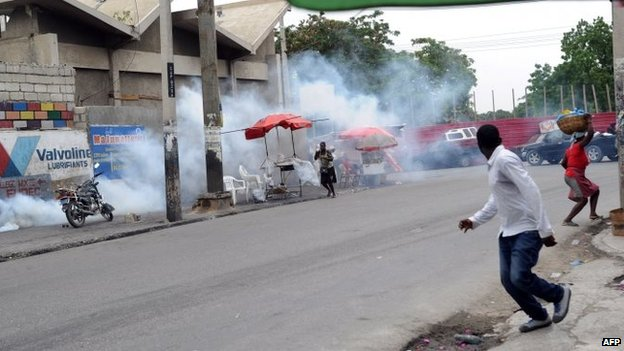 Residents flee tear gas fired by Haitian police at anti-government protesters in Port-au-Prince, Haiti, 5 June 2014