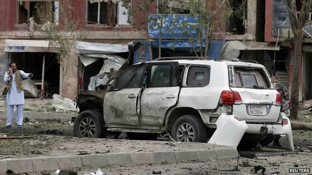 Afghan policemen investigate the site of a suicide attack in Kabul June 6, 2014.