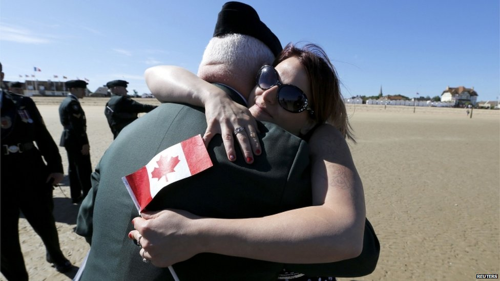 A woman holding a Canadian flag hugs a man