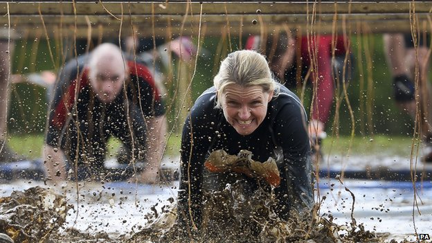 A Tough Mudder participant makes her way through electric wires