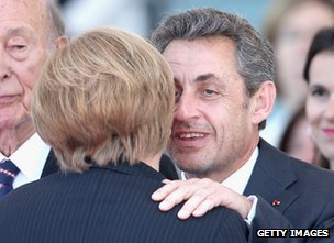 Nicolas Sarkozy embracing Angela Merkel on Sword Beach, 6 June