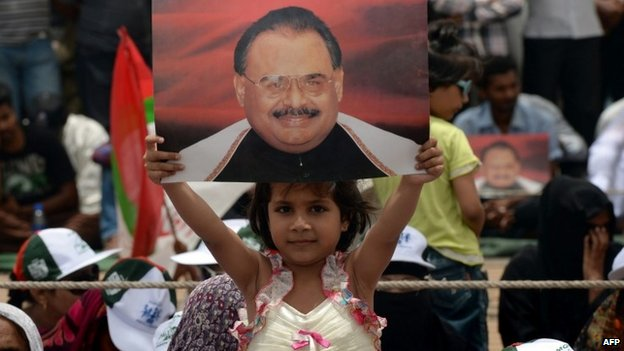 A young girl from Pakistan's Muttahida Qaumi Movement (MQM) party holds a photograph of party leader Altaf Hussain
