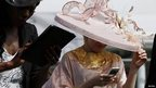 A woman looks at her mobile as she arrives for Ladies Day at the Epsom Derby Festival
