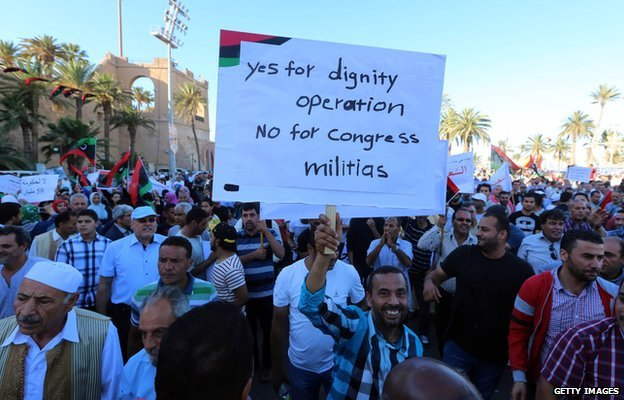 Libyans hold placards and flags during a rally in support of a rogue former general whose forces have launched a 'dignity' campaign to crush jihadist militias in eastern Libya on May 30, 2014 in Tripoli.