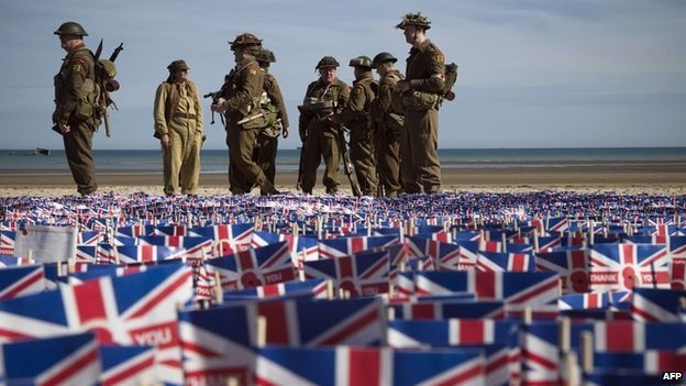 People in military uniforms on Sword Beach