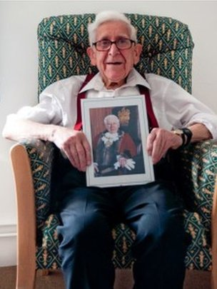 Bernard Jordan with a photo of himself as mayor
