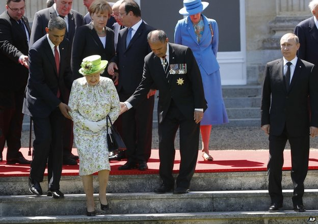 Russian President Vladimir Putin stands to the right as US President Barack Obama, left, and New Zealand's Governor-General Jerry Mateparae guide Britain's Queen Elizabeth to her position for a group photo during the commemorations for the 70th anniversary of the D-Day landings, in Benouville in Normandy, France, 6 June 2014
