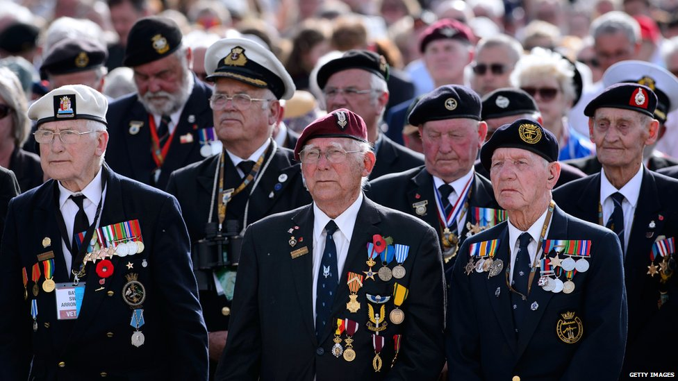 Veterans listen to a reading at a service in Arromanches-les-Bains