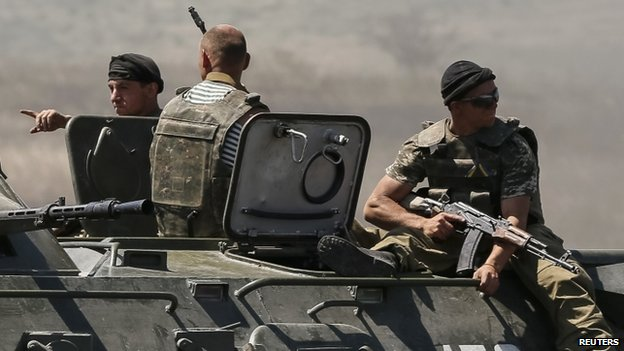Ukrainian border guards ride armoured personnel carrier along the Ukraine-Russia border near the eastern village of Marynivka. Photo: 6 June 2014