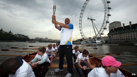 Brian Dickens carries the Queen's Baton on board the Gloriana as it makes its way down the River Thames
