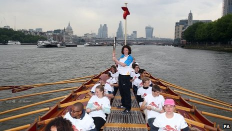 Baton-bearer Rebecca Donnelly holds the Queen's Baton on board the Gloriana as it makes its way down the River Thames