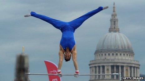 Olympic athlete Louis Smith performs on the high bars on the Millennium Bridge