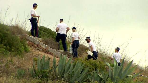 A team of police searching scrubland