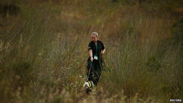 A police officer and a sniffer dog search scrubland
