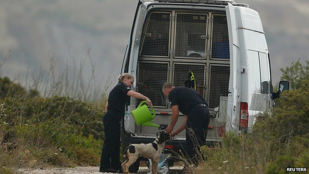 Officers pour water over the dogs to keep them cool during the search