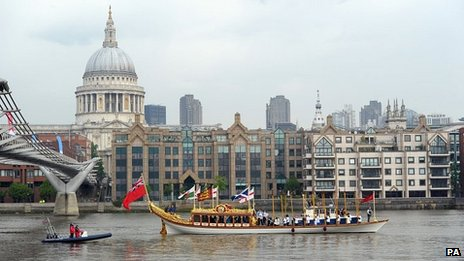 The Gloriana with the Queen's Baton on board makes its way down the River Thames