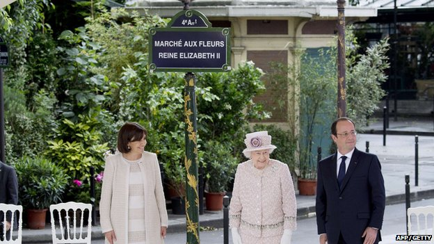The Queen unveils a sign announcing the newly renamed market