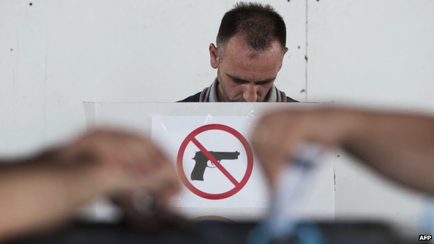 "A Kosovo Albanian man prepares his ballot at a polling booth with a ""no guns"" sign before voting at a polling station in Pristina on June 8,"