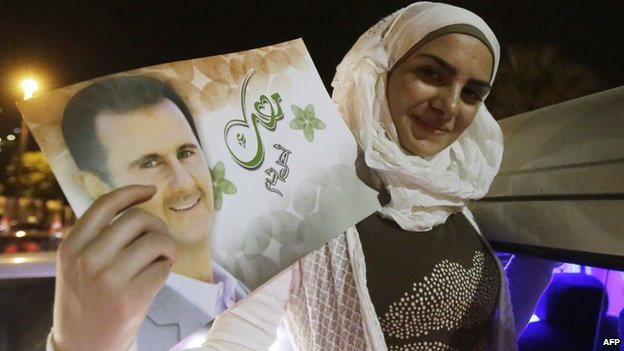 "A woman holds a picture of re-elected Syrian President Bashar al-Assad as she celebrates in Damascus after he was announced as the winner of the country""s presidential elections on June 4"