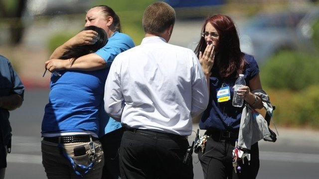 Walmart employees hug outside their store after shootings left five people dead