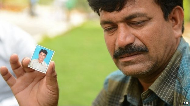 "Banoth Shekar, father of missing student B Rambabu Naik and feared drowned in the Beas River in India""s northern Himachal Pradesh state, holds a identification photograph of his son."
