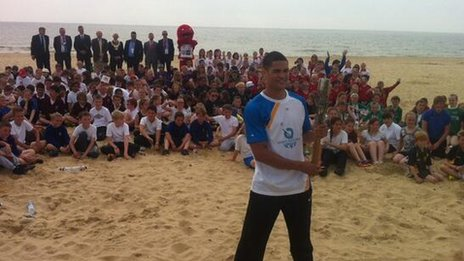 Anthony Ogogo with the baton on Lowestoft beach
