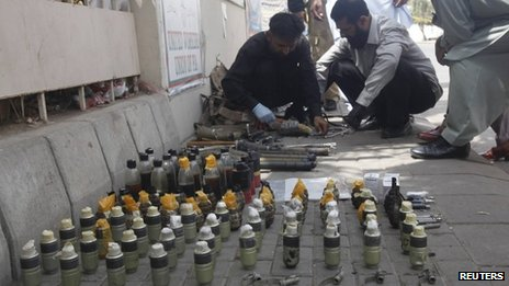Members of the Bomb Disposal Squad (BDS) defuse explosives and hand grenades along a sidewalk outside Jinnah International Airport in Karachi June 9, 2014.