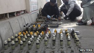 Members of the Bomb Disposal Squad (BDS) defuse explosives and hand grenades along a sidewalk outside Jinnah International Airport in Karachi