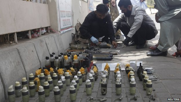Officials defuse explosives and hand grenades outside Jinnah International Airport in Karachi (9 June 2014)