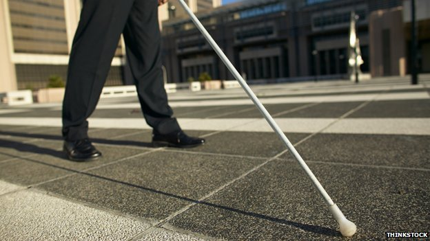 Blind person with stick walking across square
