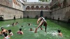 Young men jump into a well to escape the heat in Delhi.