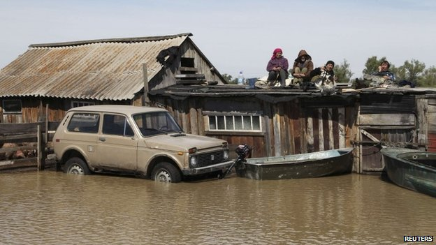 Residents in the Altai region are stranded by heavy flooding and wait on their roof for help