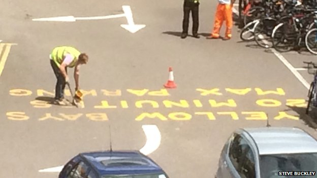 Workman painting road marking at railway station in Cambridge