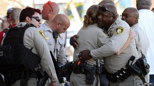 Las Vegas Metropolitan Police Department officers hug near a Wal-Mart in Las Vegas, Nevada 8 June 2014