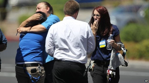 Walmart employees hug outside their store after shootings left five people dead - including two Las Vegas police officers - at the store and a nearby CiCi's Pizza in Las Vegas 8 June 2014