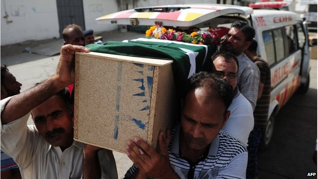 Pakistani Airport Security Force personnel carry the body of a dead colleague in Karachi (9 June 2014)