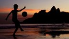 Young boy juggles a football on Ipanema Beach, Brazil. 9 June 2014