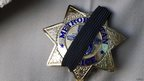 Police officer wears black ribbon over badge as police mourn two officers killed in Las Vegas