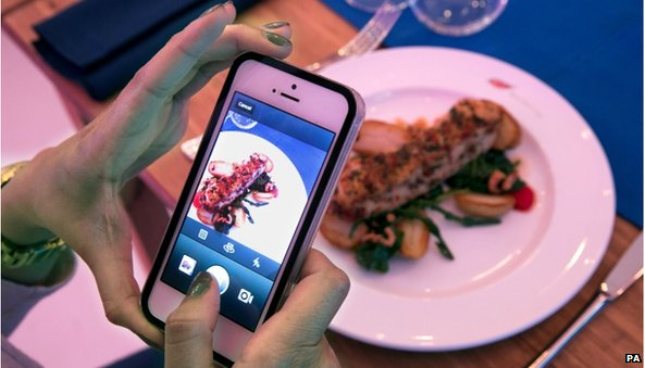 Person taking a picture of food using instagram on their phone
