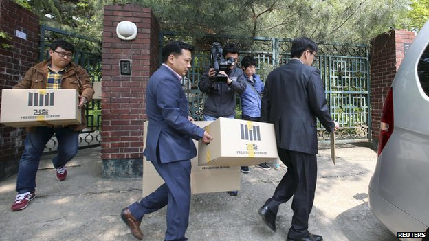 Officials from the Incheon District Prosecutors office carry boxes during a raid of the home of Yoo Byung-un, in Seoul on 23 April, 2014