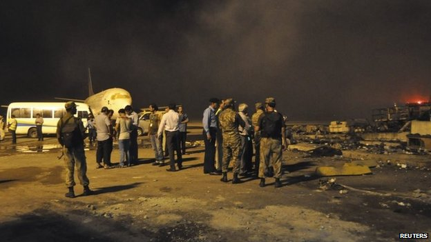 Smoke bellows as security officials and airport staff visit the site damaged by Sunday's Taliban attack on Jinnah International Airport in Karachi, 9 June 2014