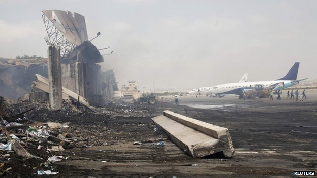 Planes near a section of a damaged building (L) at Jinnah International Airport, after Sunday's attack by Taliban militants, in Karachi