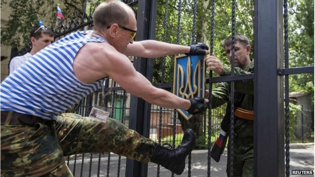 Pro-Russian separatists remove the Ukrainian coat of arms from a government building in Luhansk, Ukraine (10 June 2014)